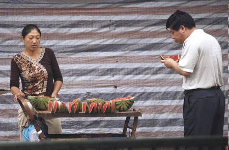 Продавщица арбузного лотка на одной из пекинских улиц. PETER PARKS/AFP/Getty Images