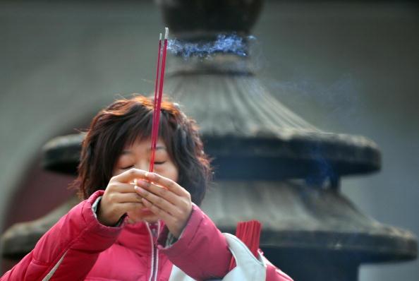 Накануне Нового года китайцы посещают храмы, возжигают свечи и молятся о счастье. Фото: Getty Images
