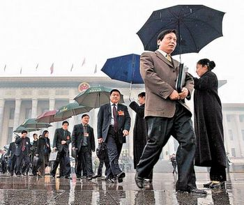 Культура чиновников компартии Китая не позволяет руководителям самим нести зонты. Фото с kanzhongguo.com