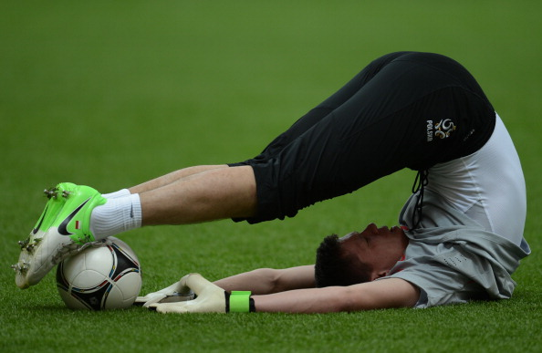 Польский вратарь Войцех Щесны растягивается во время тренировки, накануне матча открытия Евро-2012. Фото: ARIS MESSINIS/AFP/GettyImages