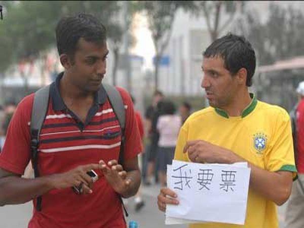 Іноземні туристи, які приїхали в Китай, тримають таблички з написом «Я хочу купити квиток на Олімпійські змагання». Фото epochtimes.com