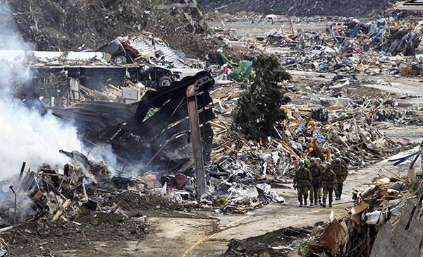 Солдаты идут по мусору, разбросанному по городу Minamisanriku в префектуре Мияги 12 марта 2011. (YOMIURI SHIMBUN/AFP/Getty Images)