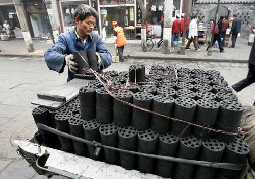 8 лютого, 2007 р. Робітники м. Сіань перевозять вугілля. FREDERIC J. BROWN/AFP/Getty Images