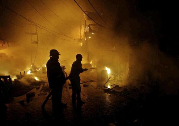 Пакистанські пожежники намагаються погасити полум'я в місці вибуху бомби у місті Лахор. Близько 15 осіб було вбито, а 40 - поранені. Фото: Arif Ali / AFP /Getty Images