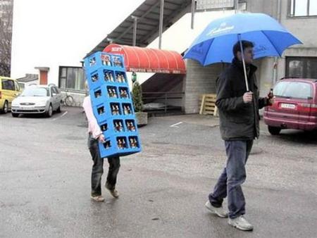 Чоловік попиває пиво і несе парасольку, а позаду його жінка ледве несе 6 ящиків пива