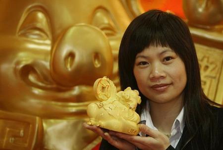 Гонгконг: женщина в руке держит украшение в виде золотого поросенка. Фото: Mike Clarke/AFP