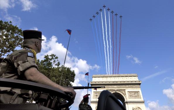 Истребители Rafale и Mirage пустили за собой красно-сине-белые шлейфы дыма как символ цветов национального флага. Франция, площадь Согласия, 14 июля 2011 года. Фото: Getty Images