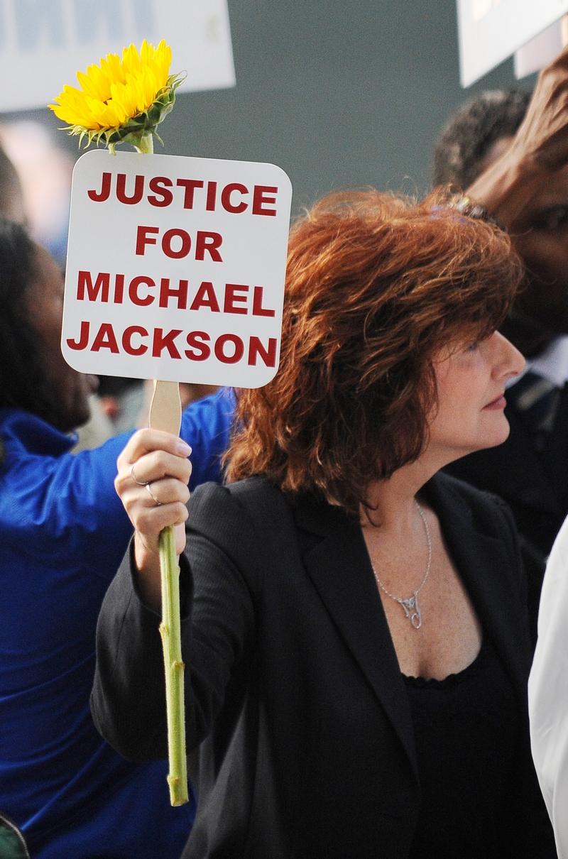 Поклонница поп-звезды Майкла Джексона за пределами здания суда держит подсолнечник. Фото: Robyn Beck/Getty Images