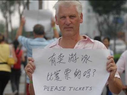 Иностранные туристы, приехавшие в Китай, держат таблички с надписью «Я хочу купить билет на Олимпийские соревнования». Фото epochtimes.com