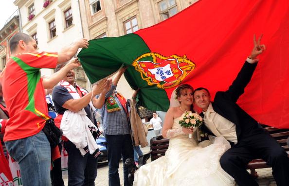 Поклонники сборной Португалии держат флаг над украинскими молодоженами на одной из улиц Львова 9 июня 2012 года. Фото: YurkoDYACHYSHIN / AFP / GettyImages