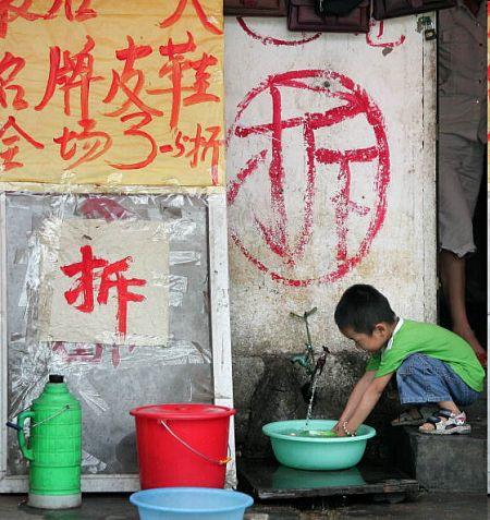 Пекин. Мальчик, набирающий воду в таз возле своего дома. Этот дом по приказу мэрии скоро будут сносить. Фото: FREDERIC J. BROWN/AFP/Getty Images