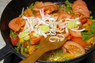 Для начинки понадобится овощное ассорти, добавляем туда лук и помидоры. Овощи тушим в сковороде на медленном огне. Фото: Владимир Бородин/Великая Епоха