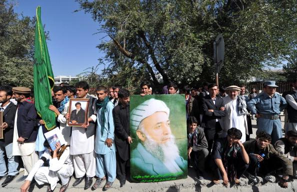 Сторонники убитого экс-президента Бурхануддин Раббани держат плакат своего кумира за пределами территории его дома в Кабуле