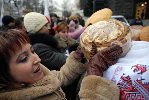 Участники митинга хлебопекарских профсоюзов выкладывают хлеб возле Кабмина во вторник 11 декабря. Фото: Владимир Бородин/Великая Эпоха