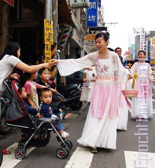 Девушки в костюмах небесных богинь раздают прохожим бумажные лотосы – символ чистоты и совершенства. Фото: Цзян Юйю/ The Epoch Times