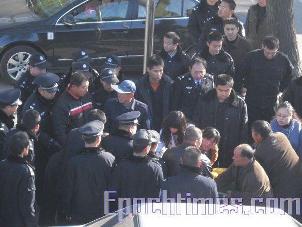 Полицейские силой забирают у родственников тело убитого Сунь Цзянцзюна. Фото: The Epoch Times