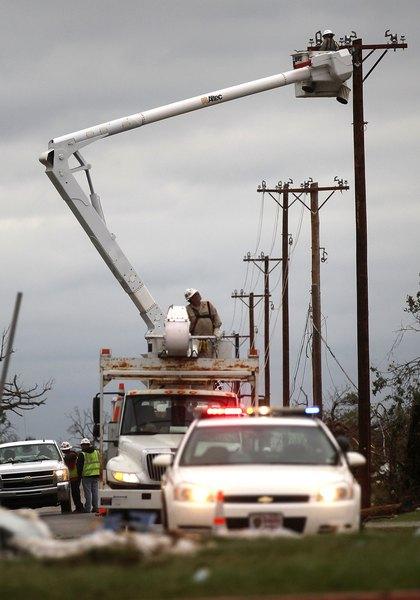 Рабочие восстанавливают поврежденные линии электропередачи. Фото: Mario Tama/Getty Images
