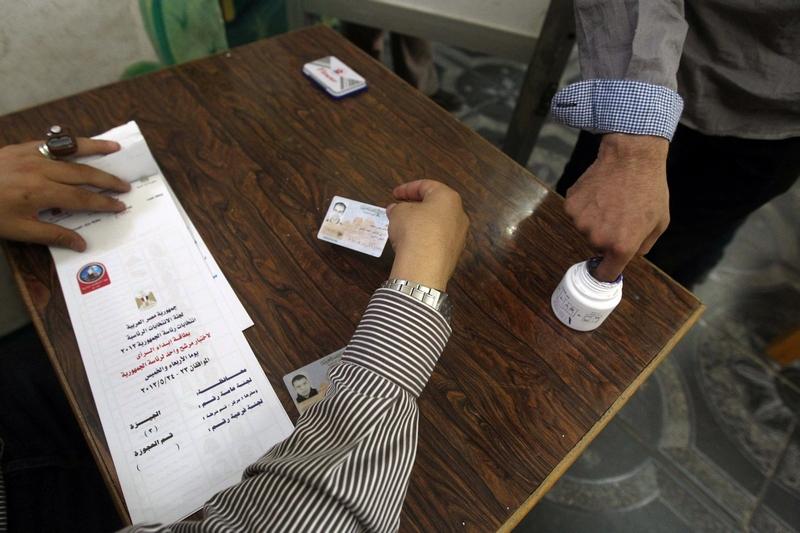 Избиратель опускает палец в чернила, чтобы поставить отпечаток напротив избранного кандидата в президенты. Избирательный участок в Каире, 24 мая 2012 года. Фото: KHALED DESOUKI/AFP/GettyImages