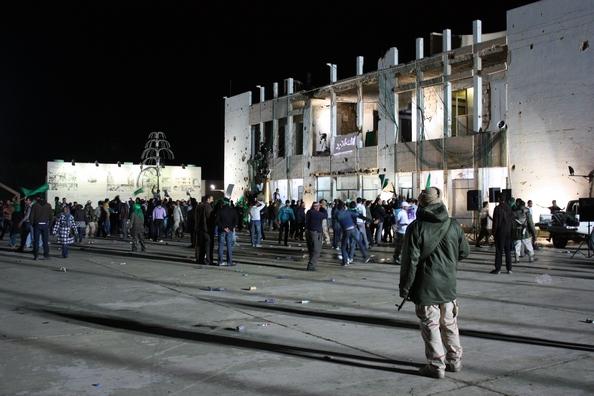 Люди ходять поблизу адміністративної будівлі резиденції лівійського лідера Муаммара Каддафі, повністю зруйнованого ракетними ударами в Тріполі, 20 березня 2011 року. Будівля, що знаходиться в 50 метрах від намету, де Каддафі зазвичай зустрічав гостей, зрі