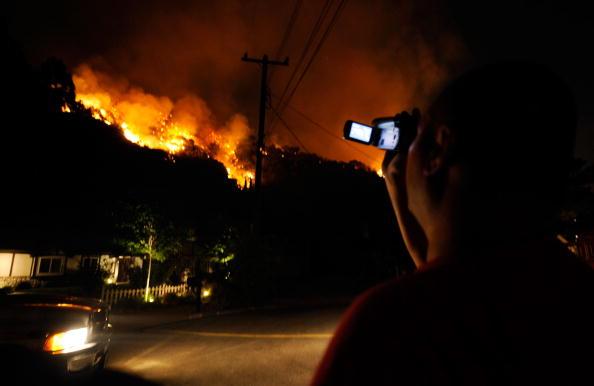 Власник дому Хенрік Айрапетян, який залишився, щоб захищати свій дім, знімає пожежу на холмі неподалік від свого дому. Фото: Kevork Djansezian/Getty Images