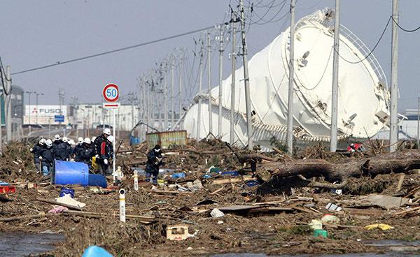 Большой резервуар лежит на поле покрытом мусором в городе Iwanuma в префектуре Мияги 13 марта 2011. (JIJI PRESS/AFP/Getty Images)