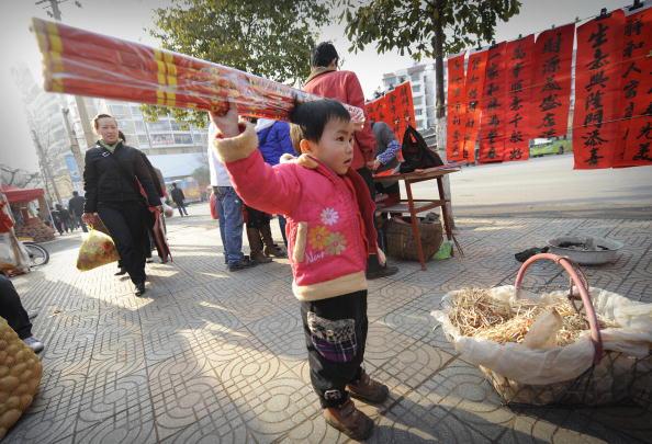 Малыш из провинции Гуйчжоу держит большие новогодние петарды. Фото: Getty Images