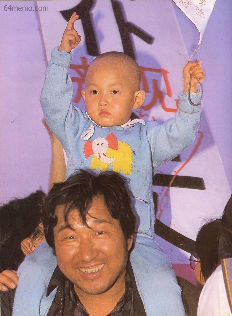 18 мая 1989 г. Малыш, сидя на плечах своего отца, держит плакат с надписью «Поддерживаю студенческое движение». Фото: 64memo.com