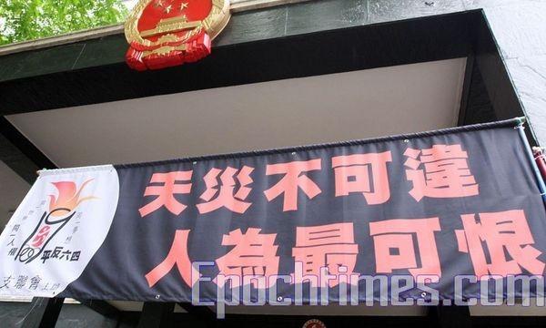 Надпись на транспаранте: «Стихийное бедствие неотвратимо, но то, что произошло по вине людей, вызывает гнев». Фото: У Ленью/The Epoch Times
