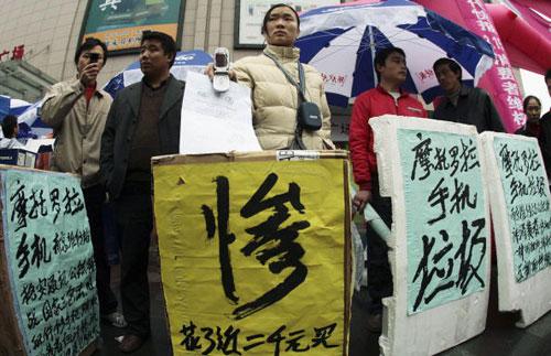 15 березня, 2007 р. Споживачі м. Наньцзін засуджують низьку якість стільникових телефонів. China Photos/Getty Images