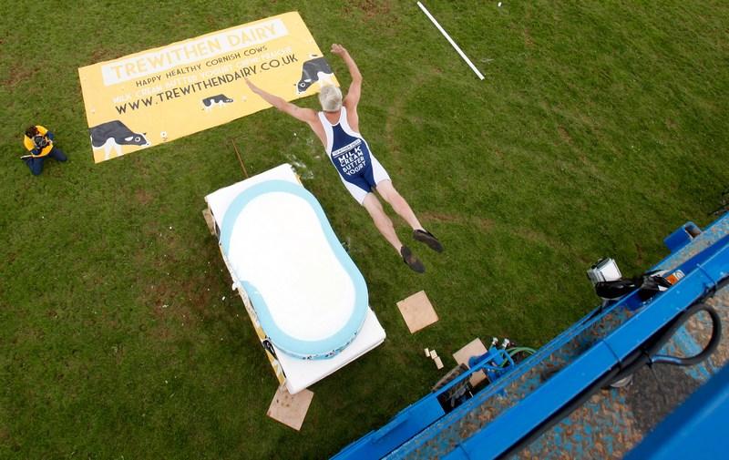 Вейдбридж, Англия, 8 июня. Американский трюкач Даррен Тейлор, он же «Профессор Плюх», устанавливает мировой рекорд по прыжку с высоты 9 метров в бассейн с молоком глубиной 30 см на Королевском шоу в графстве Корнуолл. Фото: James Ram/Handout/Getty Images