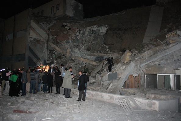 Люди стоять біля уламків ракети на купі сміття після ракетного удару, що повністю зруйнував адміністративну будівлю резиденції Муамара Каддафі в Тріполі 20 березня 2011. Будівля, що знаходиться в 50 метрах від намету, де Каддафі зазвичай зустрічав гостей,