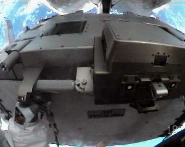 Астронавт Рональд Гаран перемещает неисправный насос системы охлаждения к грузовому отсеку шаттла «Атлантис». Снимок сделан встроенной в скафандр Гарана камерой. Фото: NASA via Getty Images