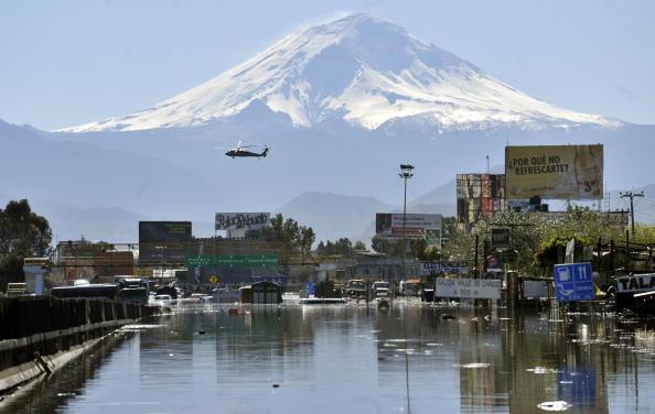 Зливи переповнили канал, в результаті чого загинуло вісім чоловік. Вертоліт пролітає над затопленим районом Валье-де-Шалько в Мексиці, 5 лютого 2010.Фото: ALFREDO ESTRELLA / AFP / Getty Images