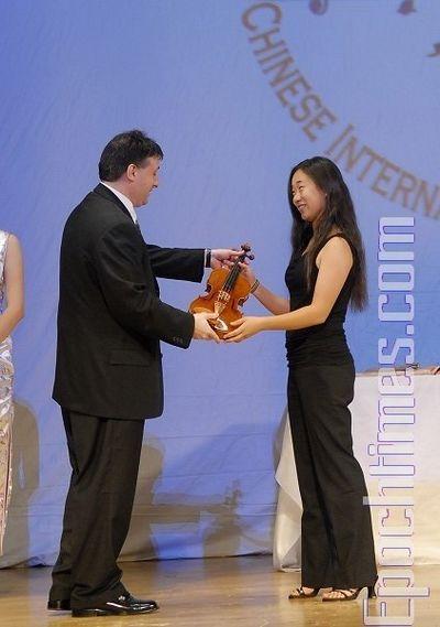Член журі Лойс Лев (Louis Lev) вручає особливий приз «висхідної зірки» - скрипку ручної роботи, конкурсантці № 9 Лі Юаньсі. Фото: Даї Бін/The Epoch Times
