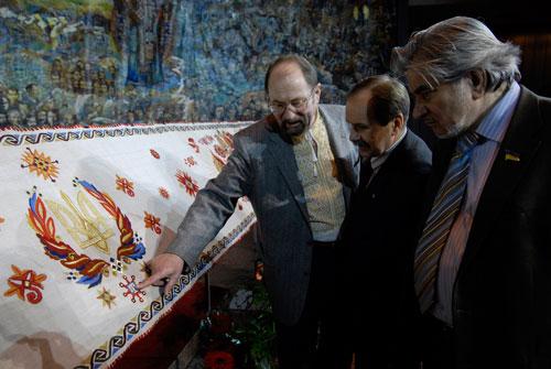 Чоловіки розглядають рушник національної єдності в Українському домі. Фото: Володимир Бородін/Велика Епоха.