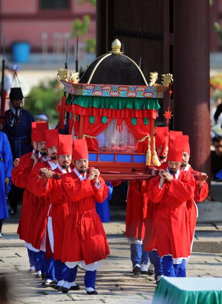 Участники торжественной церемонии несут бесценные древние книги. Фото: KIM JAE-HWAN/AFP/Getty Images
