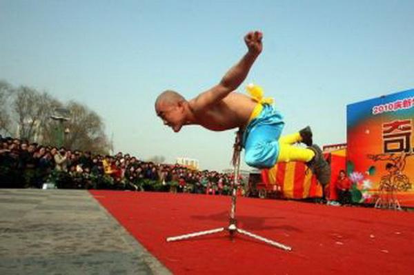 Артист балансує на сталевій палиці. Фото: AFP / Getty Images