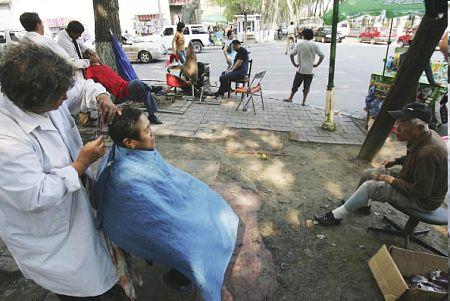 Уличная парикмахерская в Чанчунь. PETER PARKS/AFP/Getty Images