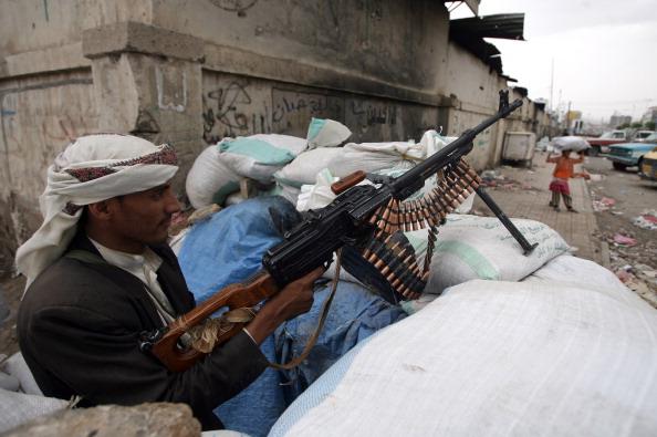 Вооруженный йеменский диссидент караулит на контрольно-пропускном пункте в Сане, 12 июня 2011 года. Йеменские оппозиционные силы GCC призвали осуществить в стране быстрый переворот власти, с тем чтобы заполнить политический вакуум, созданный отсутствием п