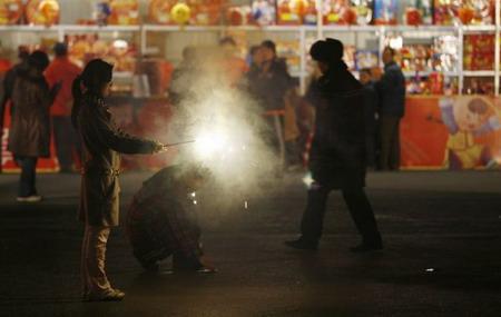 Китай, г.Пекин: перед ярмаркой молодые люди запускают фейерверк. Фото: Peter Parks/AFP