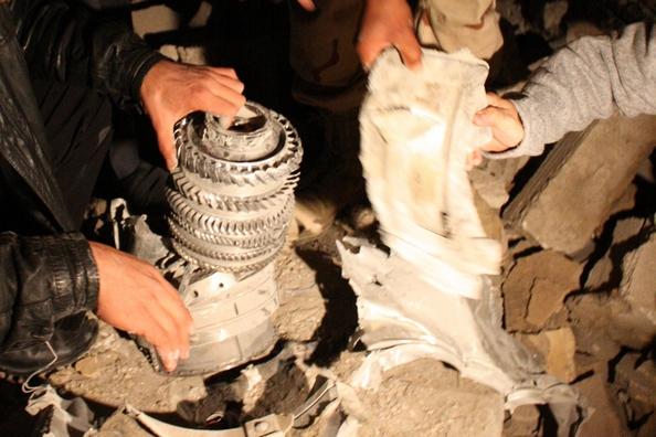 Лівійські чиновники дивляться на залишки ракети на купі сміття після ракетного удару, що повністю зруйнував адміністративну будівлю резиденції Муамара Каддафі в Тріполі 20 березня 2011. Будівля, що знаходиться в 50 метрах від намету, де Каддафі зазвичай з