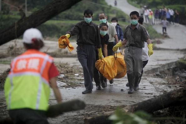 Спасатели несут тело погибшего. Провинция Хунань, Китай. Фото: STR/AFP/Getty Images