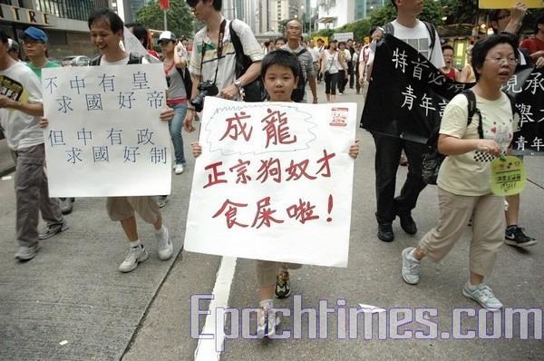 Мальчик несёт плакат: «Джеки Чан, ты низкий раб и подхалим [компартии]. Пей мочу!» Гонконг. 1 июля 2009 год. Фото: The Epoch Times