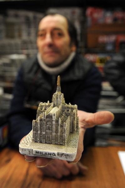 Продавець демонструє копію ліплення з глини Кафедрального собору Мілана. Італія. Фото: GIUSEPPE CACACE / AFP / Getty Images