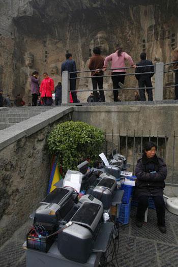 27 лютого, 2007 р. Місто Лоян, жінка продає принтери перед кам'яними печерами Лумен. Фото: China Photos/Getty Images