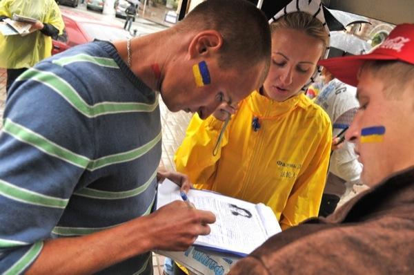Молодий чоловік ставить підпис у петиції за звільнення послідовниці Фалуньгун, яку катують у китайській в'язниці. Фото: Володимир Бородін/The Epoch Times Україна