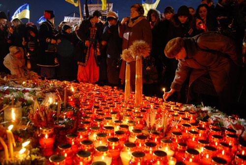 Люди ставлять свічки на вшанування пам'яті невинних жертв Голодомору. Фото: Володимир Бородін/Велика Епоха