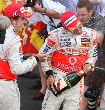 Монте-Карло, МОНАКО: Іспанський водій 'Макларен' Фернандо Алонсо (Fernando Alonso) поливає Льюіса Хемілтона (Lewis Hamilton) шампанським святкуючи свою перемогу в треку Монако. Фото: BERTRAND GUAY/AFP/Getty Images