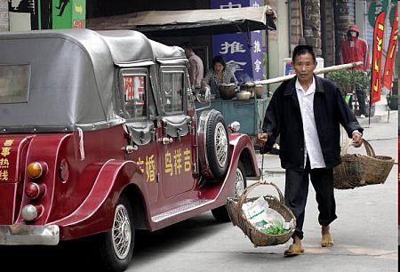 Ичан, провинция Хубэй. Старик продавец овощей проходит мимо шикарного авто. Фото: GOH CHAI HIN/AFP/Getty Images