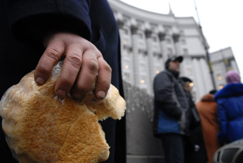 Хлеб в руке участника митинга хлебопекарских профсоюзов в Киеве возле Кабмина во вторник 11 декабря. Фото: Владимир Бородин/Великая Эпоха